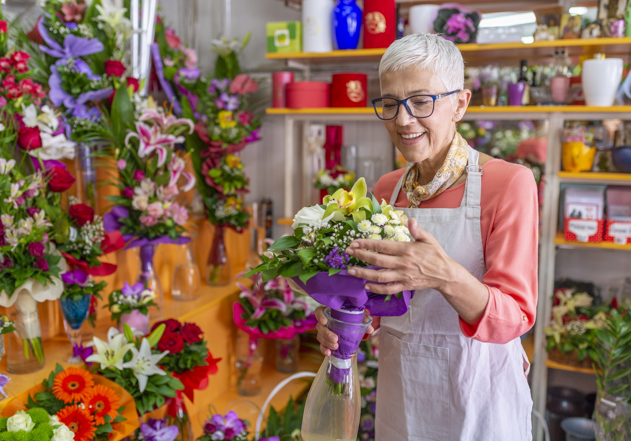 Woman working in flower shop. Smiling Mature Woman Florist Small Business Flower Shop Owner. Florist woman working in a flower shop. Small business. Flowers delivery, creating order